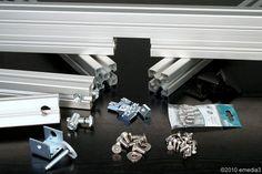 Die zum Bau des Frästischs benötigten, bereits bearbeiteten Bauteile aus Aluminium-Nutenprofil und die für Verbindungen und Anbauten erforderlichen Normteile - DIY-Bauanleitung für einen modularen Frästisch für die Oberfräse