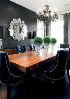 Dramatic dining room in gray with chandelier and wood table.