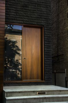 | EXTERIOR | ENTRY | lovely walnut stained entry is framed by classic black, a handsome way to enter a home #black #door entry