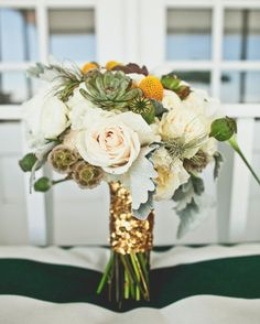 This bride carried a bouquet by Judith Bourgeois of Flora Fauna of roses, dusty miller, scabiosa pods, succulents, poppy pods, and craspedia, all tied together with a gold sequin ribbon. The bride also carried her gandmother's clover-embroidered hankie and her late grandfather's US Marine pinwith the bouquet.