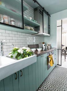 kuchnia | zielononiebieskie szafki kuchenne + białe płytki ścienne typu metro + biało-czarna podłoga