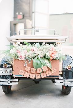 """Brides.com: . This vintage getaway car is brimming with gorgeous flowers. A New York couple added a pretty, wooden """"Just Married"""" sign to complete their look."""