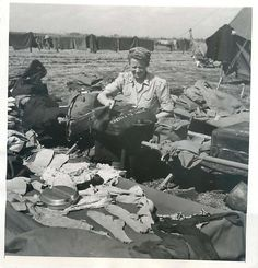1943- U.S. surgical nurse at a field hospital gathers up her clothes and equipment after her tent was blown away during a big rainstorm in Italy.