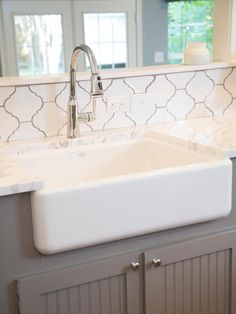 Fixer Upper - White and grey kitchen features pass through over gray beadboard, base cabinets framing farmhouse sink accented with gooseneck faucet paired with white quartz countertops and white arabesque tile backsplash, Home Depot Merola Tile Provenzale Interior, Home, Fixer Upper House, Moroccan Tile, New Homes, Home Renovation, White Farmhouse Sink, White Moroccan Tile, Farmhouse Backsplash