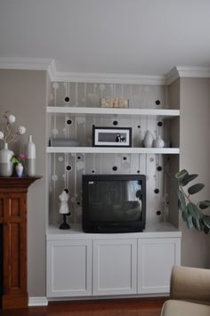I really like the idea of wallpaper behind shelves! I am thinking tan or beige walls and some sort of blue wallpaper!