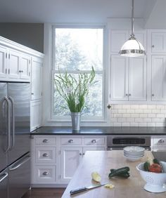 white cabinets, subway tile, butcher block on island, dark counters
