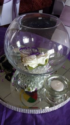 Fishbowl centrepiece with clear diamonds, ivory roses and purple butterfly #weddingcentrepiece #fishbowl #purple