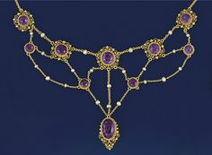 An Edwardian gold, amethyst and seed pearl necklace   Composed of amethyst filigree panels suspended from a fine belcher-link neckchain with seed pearl and chain-link swags supporting a central amethyst drop and connecting panels, approximately 39.0 cm. long, and a pair of earpendants ensuite