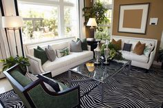 Living room design with two white sofas taupe walls and zebra area rug.  Glass…
