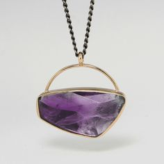 """An oxidized sterling sliver and 14k yellow gold necklace with an asymmetrical sterling silver backed faceted amethyst in a handle pendant on a 24"""" chain. Stone measures approximately 5/8"""" x 1"""" by Jamie Joseph."""