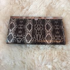 NWOT Bebe Black and Silver Python Clutch Wallet This NWOT Bebe black and silver snakeskin print clutch/wallet is perfect for a night out! Has many pockets on the inside. Never worn - in perfect condition. bebe Bags Clutches & Wristlets