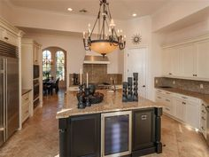 U shaped kitchen with cream cabinets and dark wood island with beige granite counters