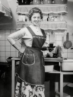 Een huisvrouw met schort aan poseert trots in haar keuken met een kopje koffie.