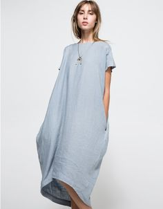 A lightweight, short-sleeved linen dress in sky blue. Features light woven linen material, wide rounded neckline, fringe shoulder seam accents, seam slip pockets at sides, rouched fabric along back yoke, long oversized structure, rounded high-low hem and