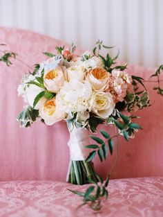 peachy garden roses, white peonies, ivory garden roses, blush stock flowers, white ranunculus, jasmine vine and olive branches wrapped in ivory ribbon with the stems showing.