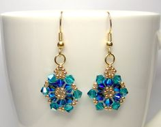 Blue and green earrings  A pretty pair of swarovski flower earrings made using blue ziron AB and montana blue ABx2 swarovski elements and woven together with galvanised gold seed beads. The earrings are quite lightweight.  The size of the earring across is 1.75 cm (0.7 inches). These are the larger swarovski elements star earrings, smaller ones are also available  The fish hook is silver plated.  Length of earrings, without the fish hook are 2.5 cm (1 inch)