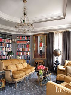 Designer Couple Takes Home To Palatial Level. THE LIBRARY: In homeowner Larry Hokanson's library, a mustard gold sofa was inspired by the color of Russian palaces; the chevron rug is custom by Hokanson. Draperies are by Schumacher and Beacon Hill; linen sheers by Duralee. The painting of the Russian guard was acquired in St. Petersburg.
