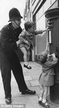 A policeman in the 50s helps a young child post a letter. An era when a policeman commanded respect and it was quite accepted to get a clip round the ear if he thought you deserved it for doing something wrong. How times have changed!