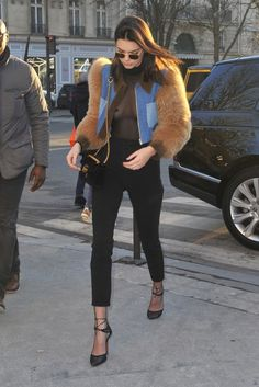 Kendall Jenner is always one of our street style stars! We collected the models' best fashion moments. Here, she is wearing a black bodysuit with a fur-sleeved jacket in Paris.