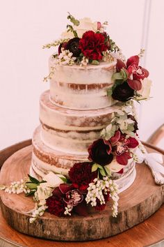 Semi naked wedding cake with trailing red carnations and burgundy orchids on a rustic wood round | Popcorn Photography