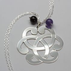 Un Collier en argent avec un motif très tendance symbolisant la Connection entre le Ciel avec une pierre gemme améthyste et la Terre avec une perle de pierre gemme de grenat sur cristalange