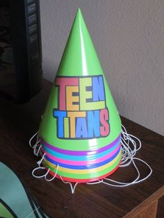 I bought plain party hats at Wal-Mart.  I got full sheet labels (sticker paper) at an office supply store.  I printed the Teen Titans logo on the label paper, cut them out and stuck them on the hats.