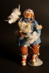 Yupik Eskimo Dancing Doll This hand crafted doll was created by Shelley Chamberlain using multiple different types of fabric for the kuspuk and cotton wood for the face. Shelley is a Yupik Eskimo from the village of Bethel, Alaska. Dimensions - L: 5in. H: 11in.  This is a traditional style yupik doll with kuspuk and head dress made with beads.