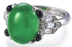 An art deco jadeite jade and diamond ring, circa 1925,     centering an oval cabochon jadeite jade, measuring approximately 10.7 x 13.4 x 5.5mm., with round cabochon onyx detail, baguette and round brilliant-cut diamond shoulders and a beveled mount; mounted in platinum; size 6. Via Bonhams.