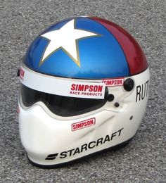 """Johnny Rutherford 1989 Starcraft Simpson Bandit helmet. This replicates the helmet worn at Indianapolis where """"LONESTAR"""" JR qualified a Glidden Menards Lola Buick, but was bumped from the field. He made a late attempt in one of AJ Foyt's Copenhagen Lola's but failed to make the race"""