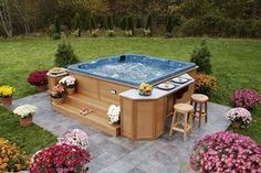 This outdoor hot tub made with wood is beautiful, comfortable and luxurious. The side bar and counter enables you to enjoy a drink or snack while relaxing yourself in the hot tub. The bright colored flowers all around the platform are increasing the natural beauty of the patio.
