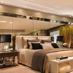 Quarto super luxuoso com destaque para o painel espelhado por trás da cabeceira da cama. Projeto Paty Franco e Claudia Pimenta Via Pn Arquitetura