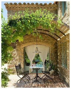 Arched pergola over stone farmhouse patio dining area. pergola french country Hello Lovely - Inspiration for Interiors