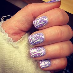 Marbled lilac nails with stamped flower pattern.