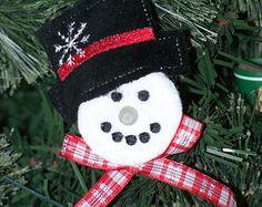Zijn dit niet gewoon de liefste?  Set van 4 Snowman ornamenten gemaakt met behulp van batterij theelichtjes. Alle hebben zwarte hoge hoeden met een sneeuwvlok geborduurd op het. Elk heeft een fleece sjaal aan hatband.  Deze zijn zo schattig als hun neus verlicht zijn opknoping op uw kerstboom. Alle zijn voorzien van de batterij, met een aan/uitschakelaar. Batterijen zijn vervangbaar.  De sneeuwmannen hangen aan een geborduurde overeenkomende snoer. Hang ze op uw eigen boom of geef ze als…