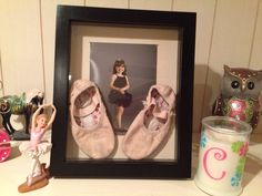 First pair of ballet shoes in shadow box with first ballet picture.