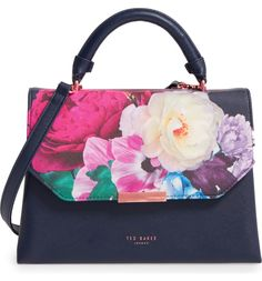 Ethereal blossoms color this ladylike structured bag designed with twin interior compartments for easy organization, while a flat base, optional, adjustable crossbody strap and rolled top handle enhance the style's convenience.