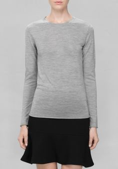 Made from soft wool, this basic sweater has a clean, simple design.