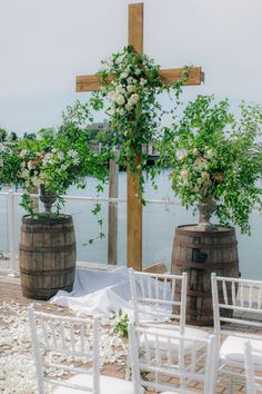 Romantic wedding in Bay Harbor Michigan. Wedding ceremony with wooden cross and wine barrels and lots of greenery. Photo by Clane Gessel. #greenerywedding #weddingceremony