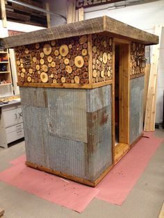 custom sauna - i love the roughness to this one, the tin sheets and the log rounds. nice contrast