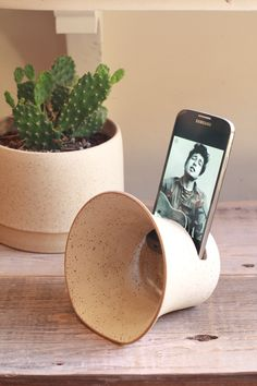 Hand crafted ceramic phone amplifier with hole for charger cord. Listen to music anywhere with this minimalist piece. Glazed in matte speckled white.