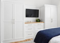 White built-in wardrobes flank a built-in dresser accented with a wood top and fixed beneath at flat panel television. Built In Bedroom Cabinets, Bedroom Built In Wardrobe, Bedroom Built Ins, Built In Dresser, Bedroom Closet Design, Tv In Bedroom, Wardrobe Tv, Wardrobes For Bedrooms, Built In Wardrobe Designs