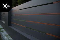 Flow is modern aluminum fence with Rockina Cubero walls and unusual version of the Horizon Massive panels. //  W nowoczesnym ogrodzeniu aluminiowym Flow wykorzystano mury i podmurówki Rockina Cubero oraz nietypową wersję systemu Horizon Massive. Jako okładzinę murów zastosowano trwałe i efektowane spieki kwarcowe w kolorze ciemnoszarym. W poziomych przerwach pomiędzy szerokimi aluminiowymi profilami umieszczono wstawki drewnopodobne. Gate Wall Design, Steel Gate Design, Front Gate Design, House Gate Design, Gate Designs Modern, Modern Fence Design, Modern Gates, Entrance Gates, House Entrance
