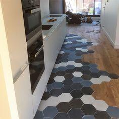 Mélange de parquet et carreaux de ciment hexagonaux, dans un dégradé de bleu et gris, réalisé en collaboration avec l'agence d'architecture Akiko à Bordeaux
