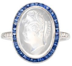 Black Starr & Frost Belle Epoque moonstone cameo sapphire ring.    Circa 1910.  A Belle Epoque carved moonstone cameo ring, the portrait cameo with a calibre cut sapphire surround in a fine diamond set platinum mount. Listing via 1stdibs.