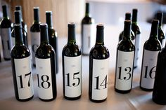 Table numbers for wedding?  More simple, you could add a tag with number on a bow, and keep the original bottles wih labels in tact.