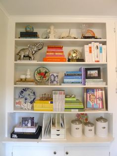 Well organized book shelf..  good tip to remove the paper covers from hard back books and group in colors