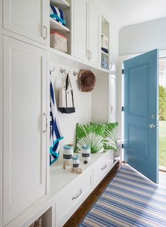 Chic cottage mudroom features a wall of floor to ceiling built in mudroom cabinets flanking a mudroom bench with drawers under overhead shelves.
