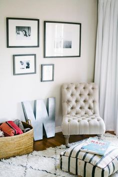Chic nursery features a black and white photo wall over a tan linen tufted slipper chair, Anthropologie Linen Orianna Slipper Chair, next to a zinc letter alongside a Amala Floakti Rug.