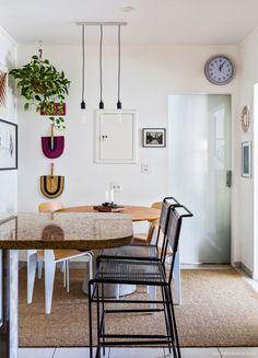 Apartamento na cidade cheio de charme, com luminárias pendentes, plantas e decor na parede.