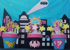 Emma's Superhero Girl Birthday Party...... centerpieces are painted terra Cota pots with cut out logos and signs, with a little tulle and pipe cleaner for springs, backdrop city made from cutout cardboard and paper windows against a blue tablecloth with star stickers and a cutout bat signal. (Paperkat Designed)